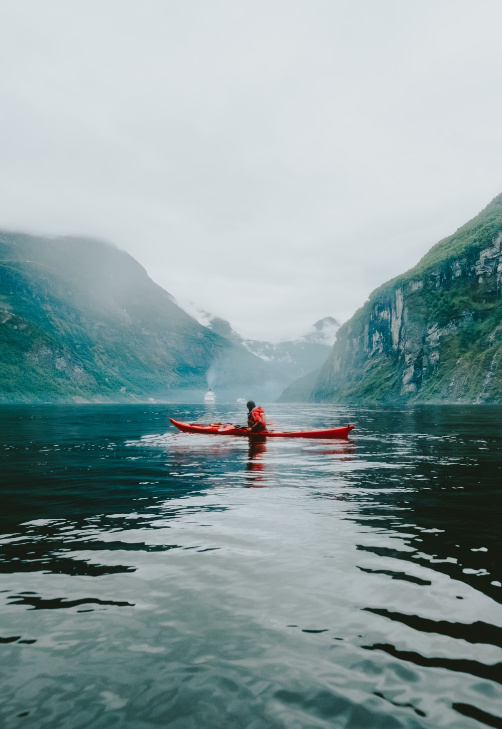 person riding kayak on body of water