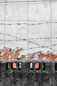 white concrete wall with orange and red graffiti