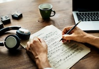person writing on paper with music notes