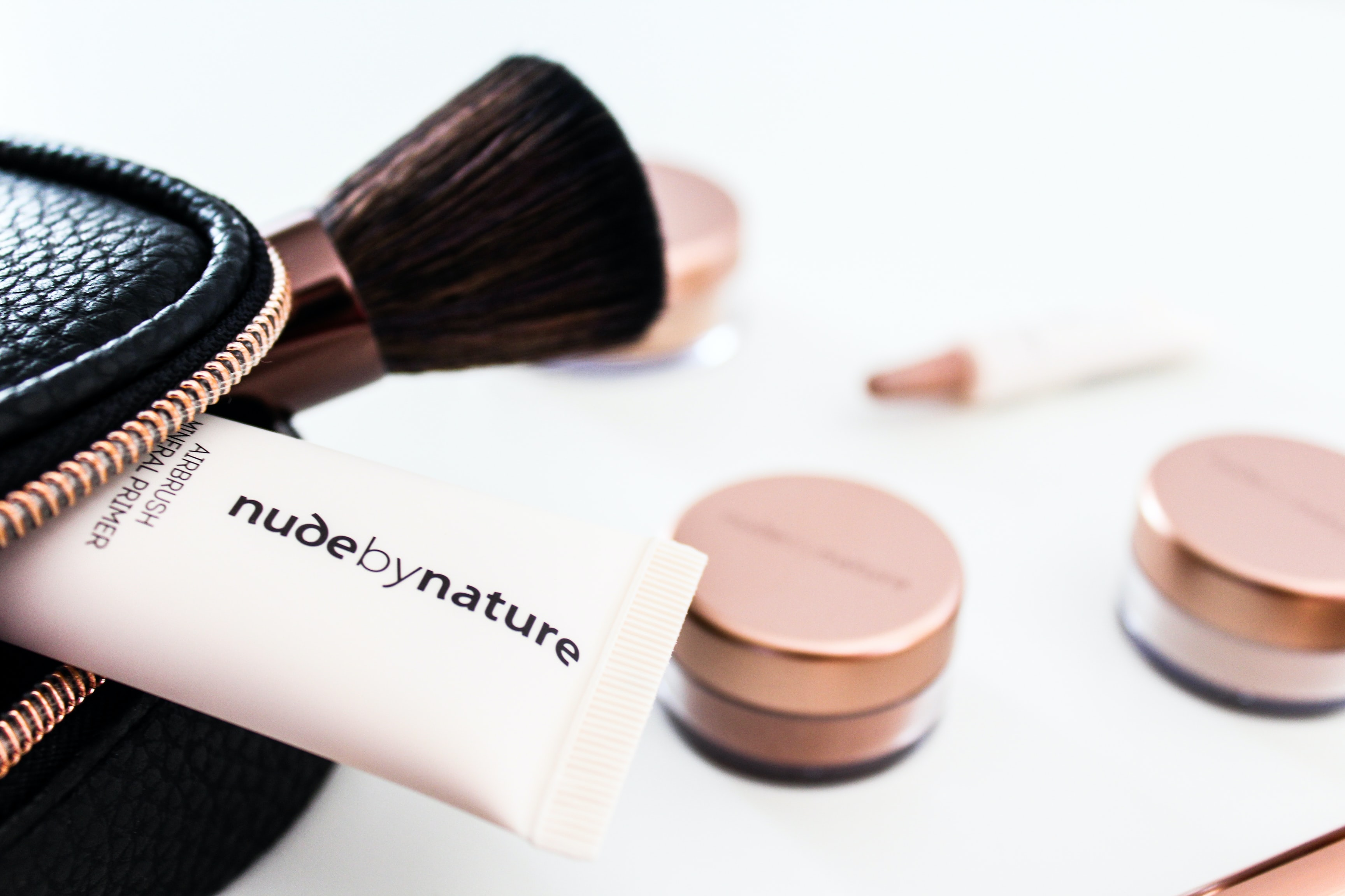 Nude by Nature soft-tube beside brown makeup brush