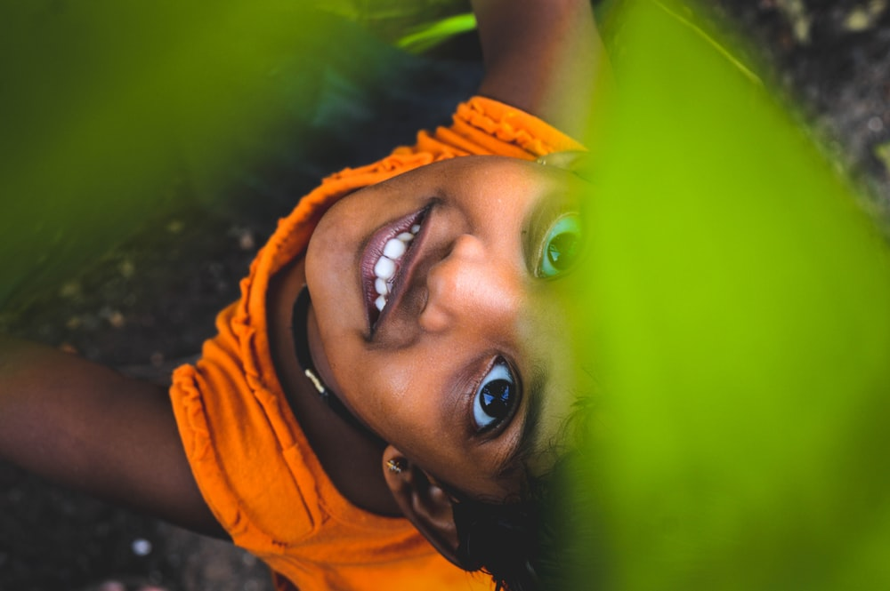 smiling girl under green leaves