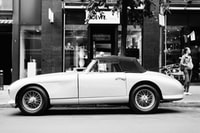 greyscale photo of classic convertible coupe on road