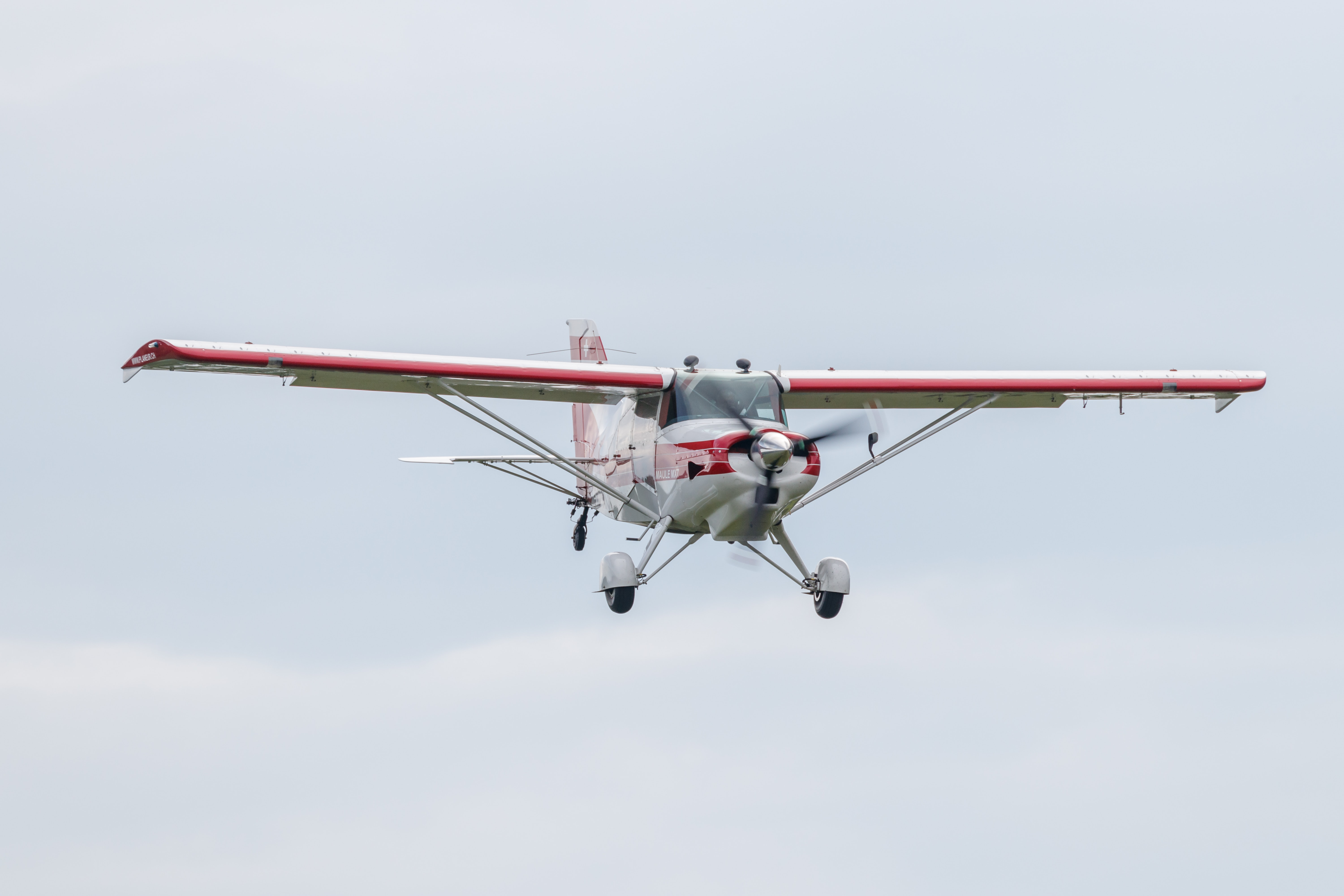 flying red and white biplane during daytime