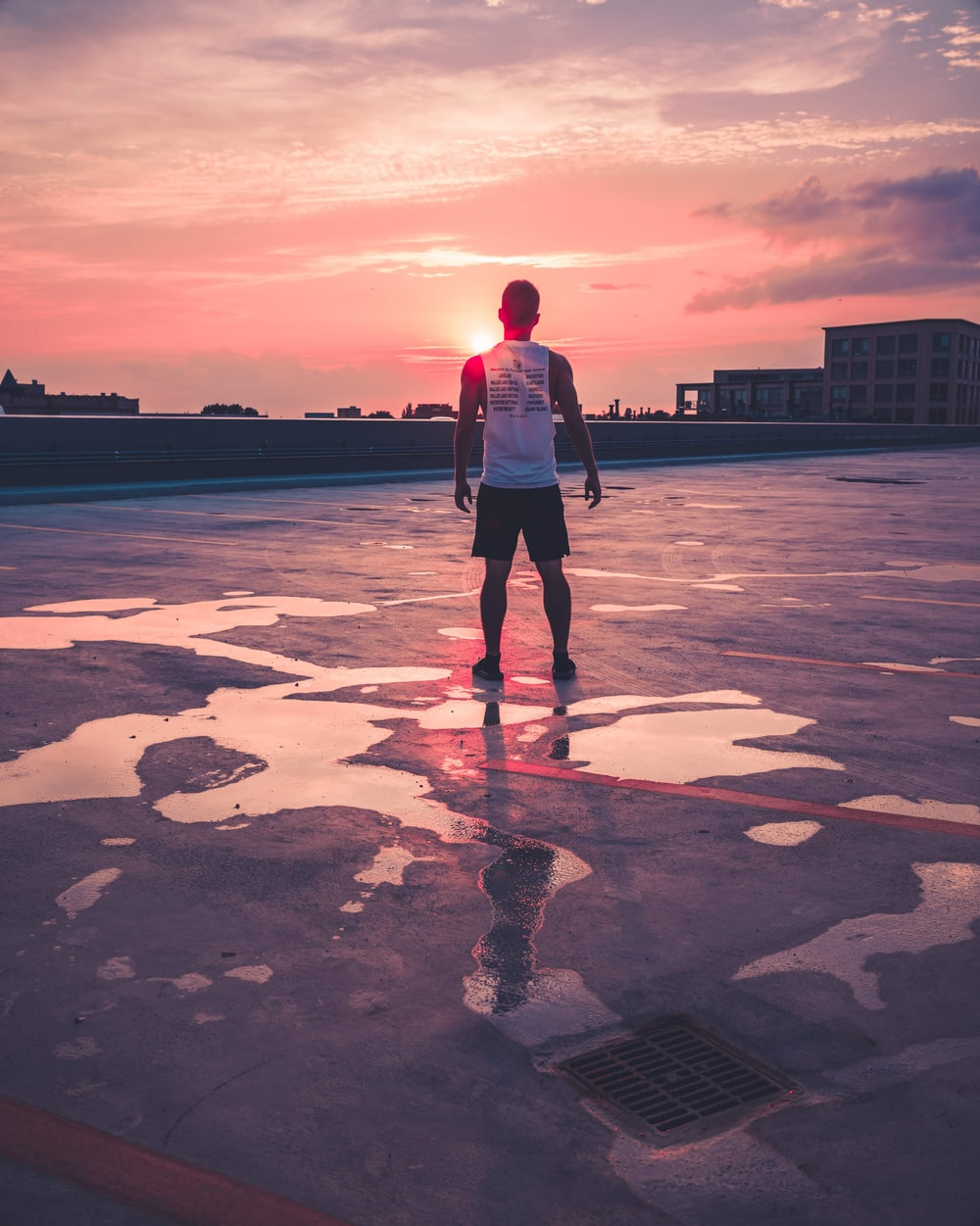 man standing above gray concrete area facing large buildings at golden hour