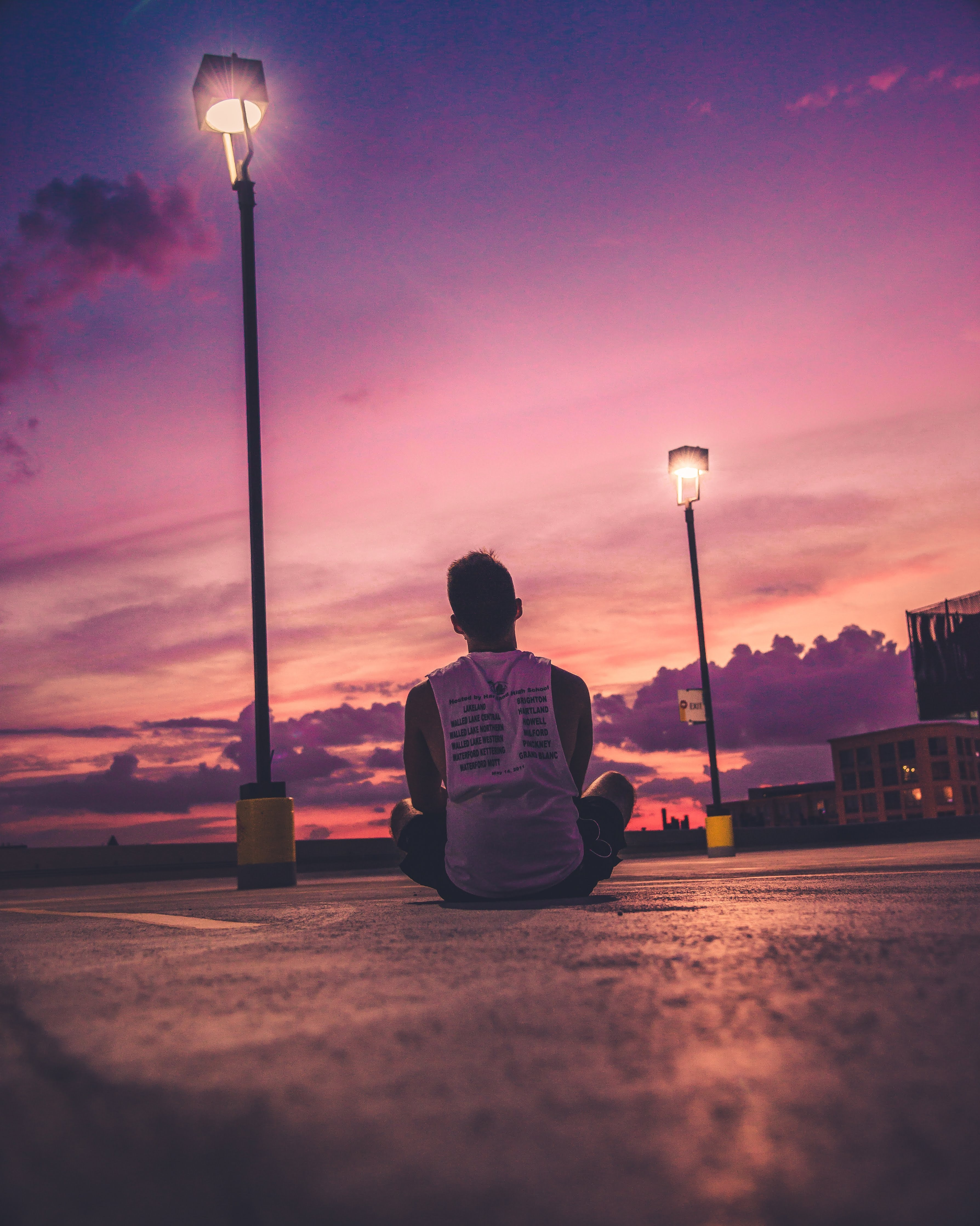 man sitting on road near turned-on black post lamp during sunset