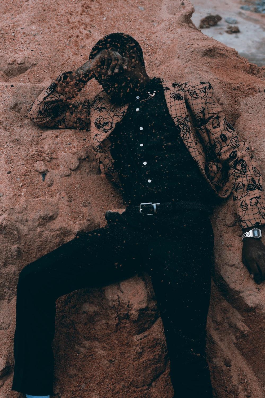 man wearing brown jacket lying on sand