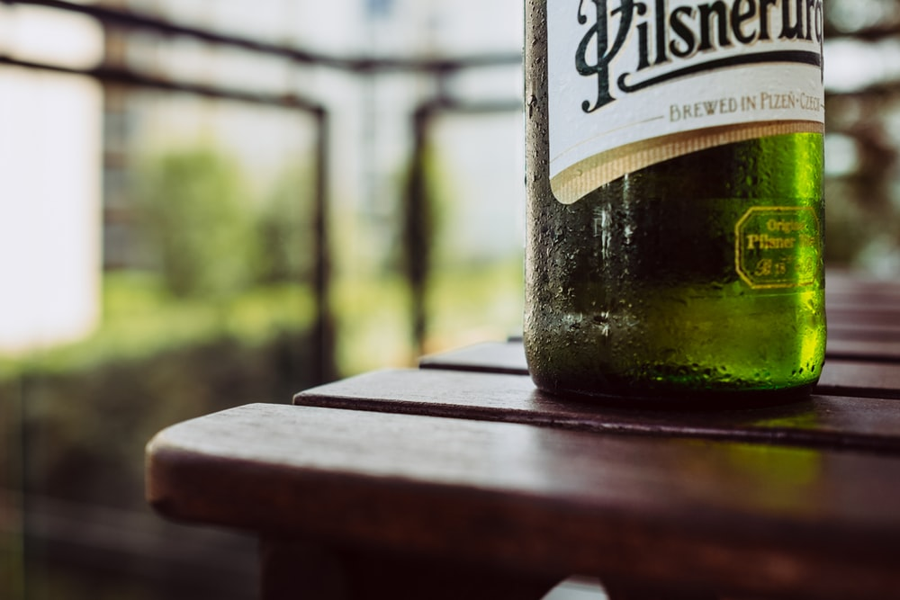 green wine bottle on brown wooden table