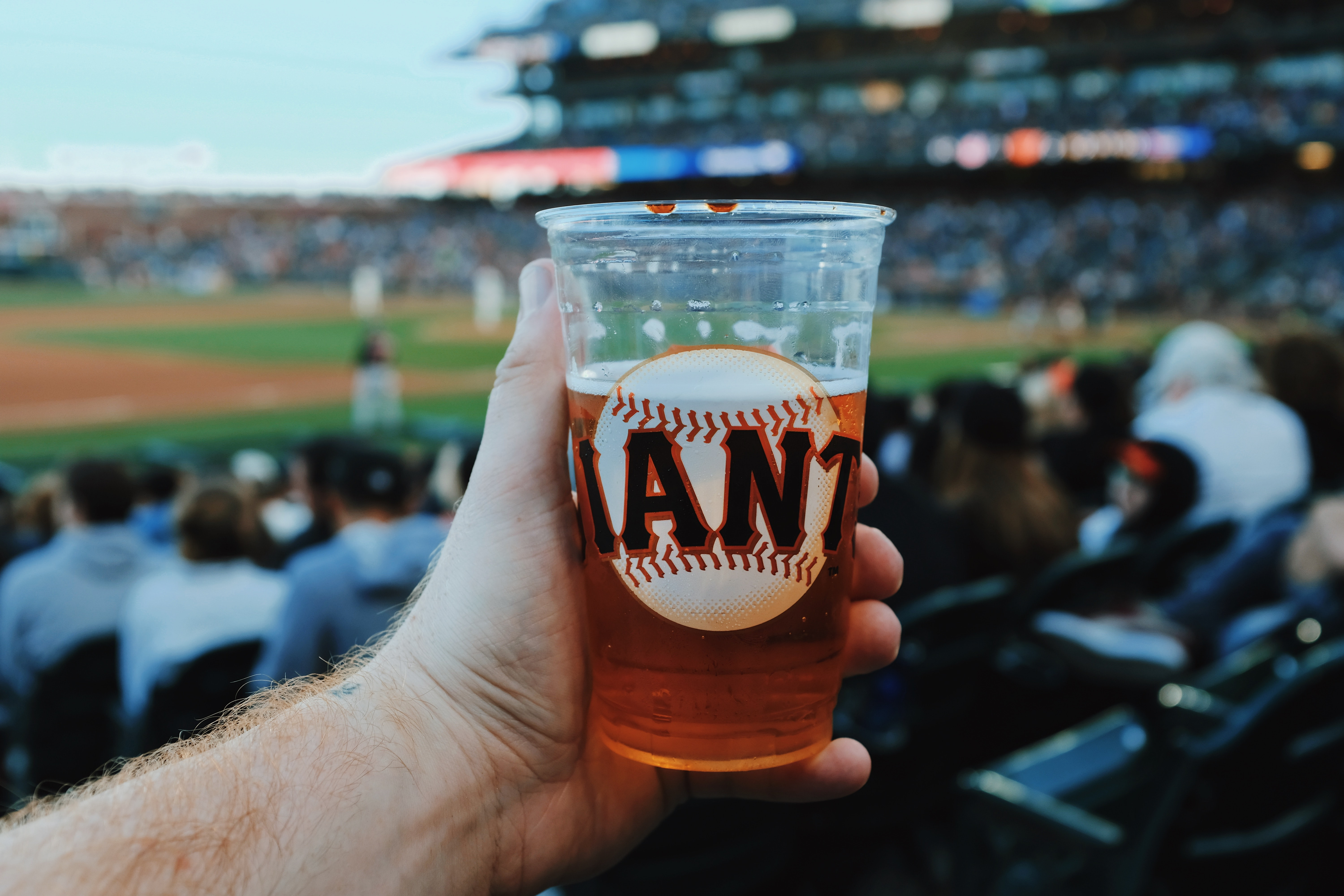 person holding clear plastic cup with beer