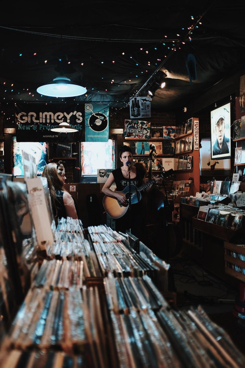 woman sings while playing guitar
