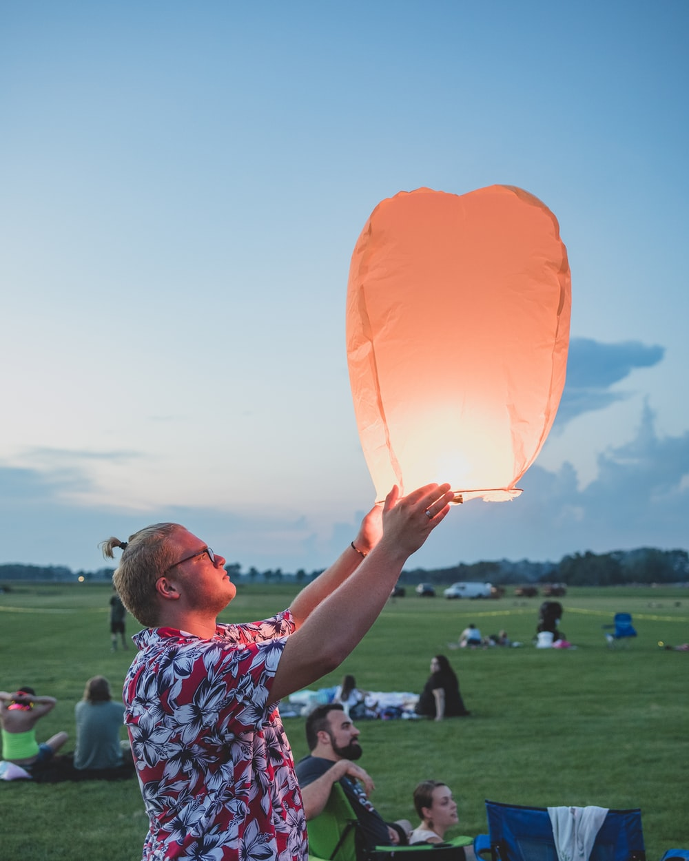 man holding flying lantern in park
