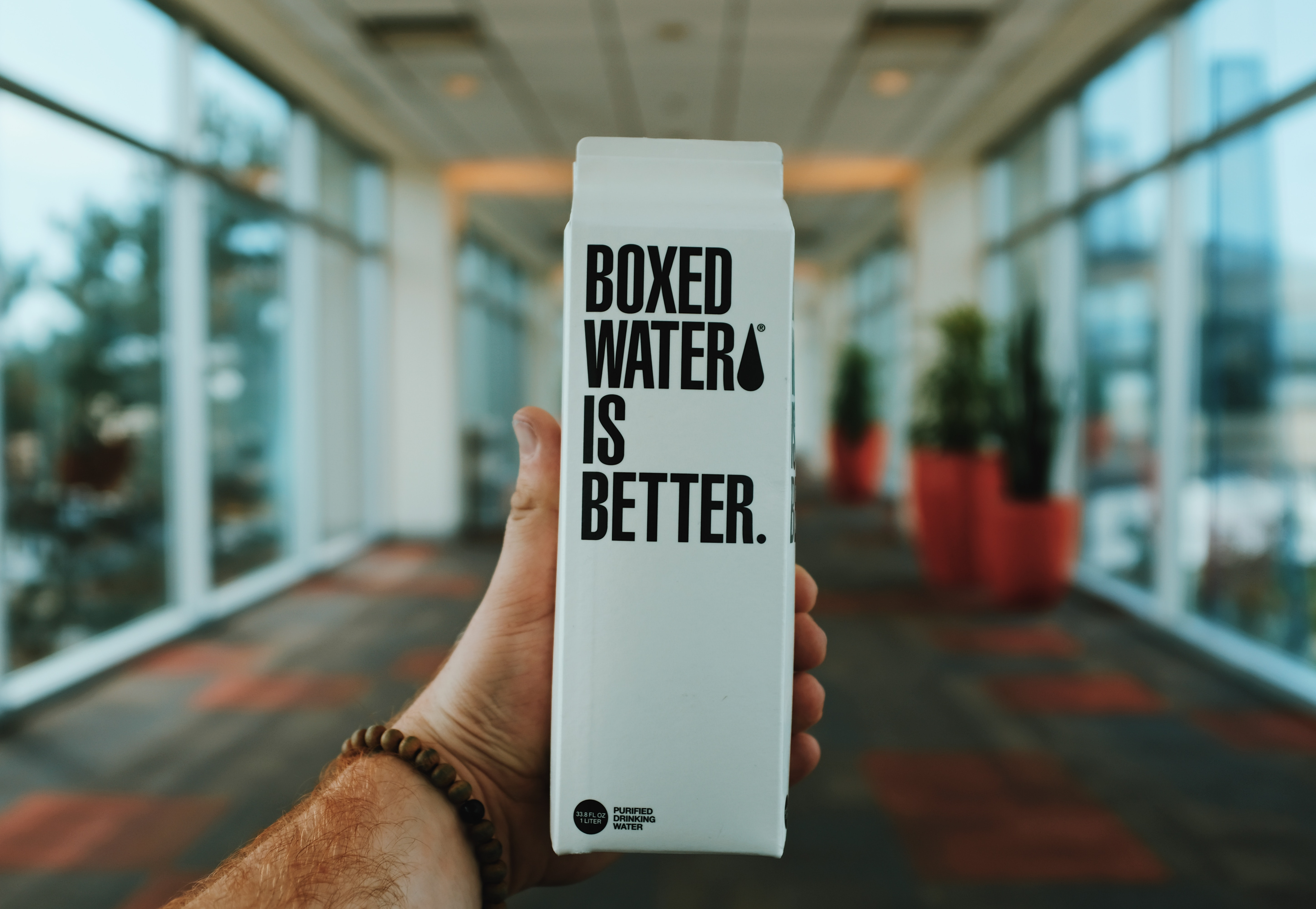 person holding boxed water is better box