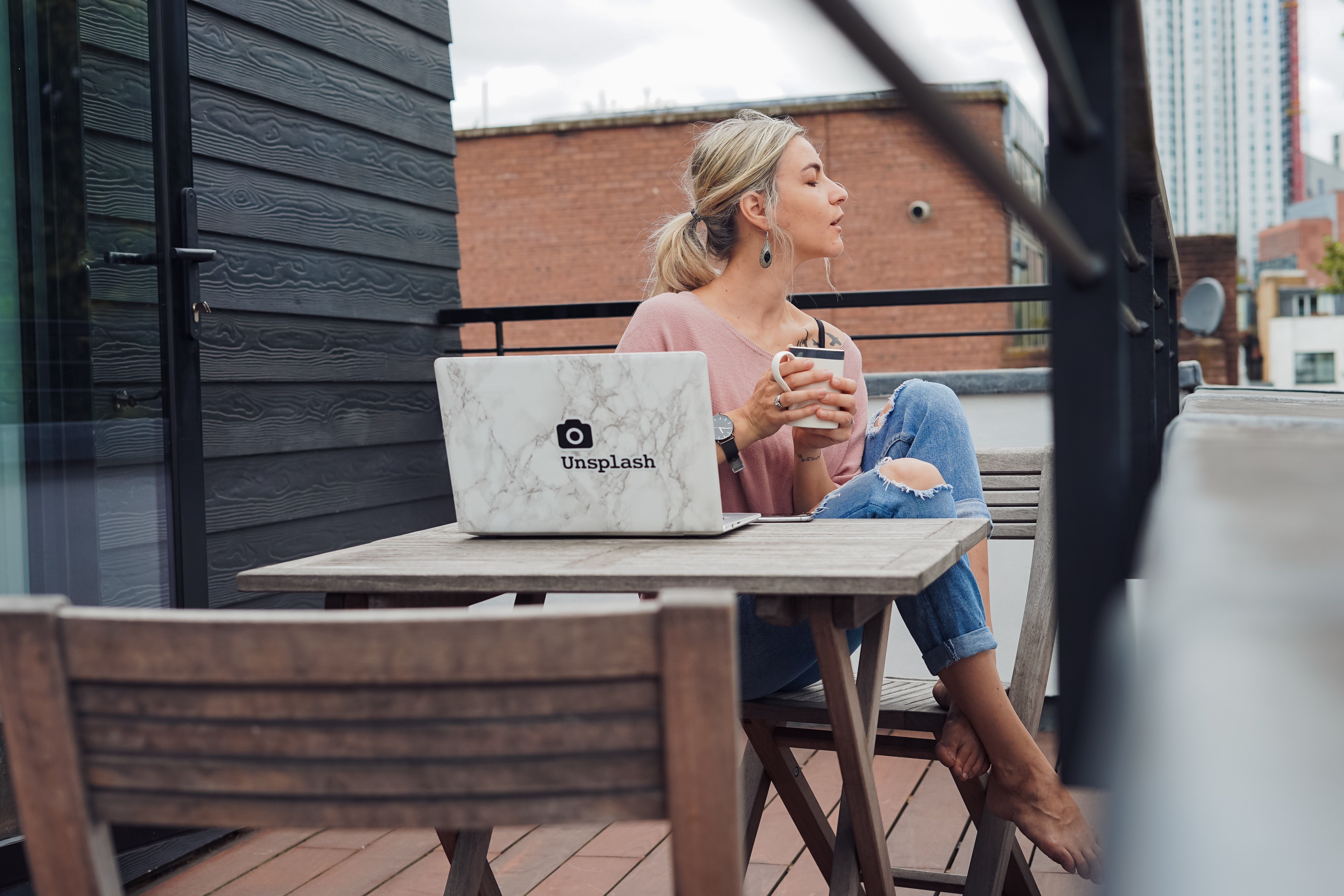 woman sitting on gray wooden chair beside rectangular table with white laptop at daytime