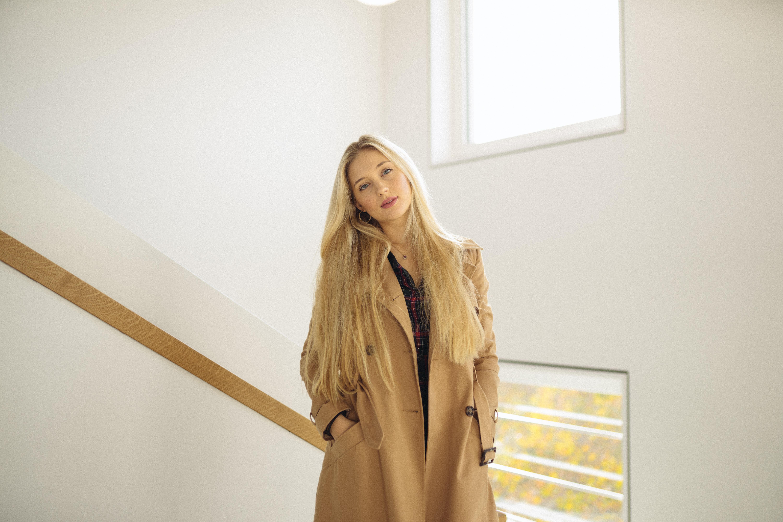 woman wearing brown coat standing in stair