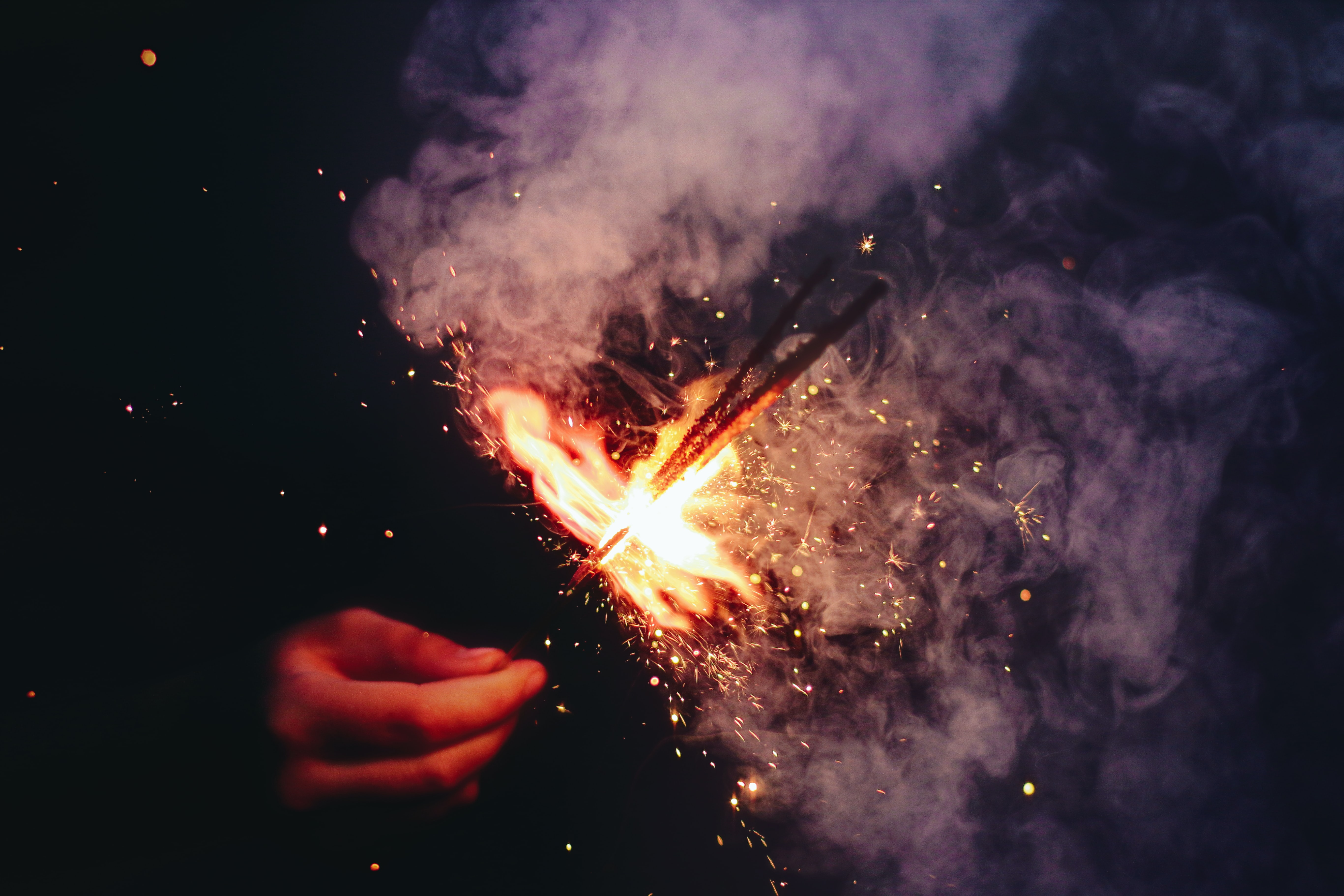 person lighting the sparkler with smoke