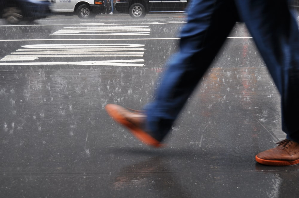 man wearing blue pants walking on street