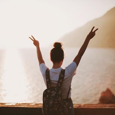woman standing near seashore doing peace sign