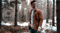 man wearing white turtleneck sweater with brown jacket while standing in forest