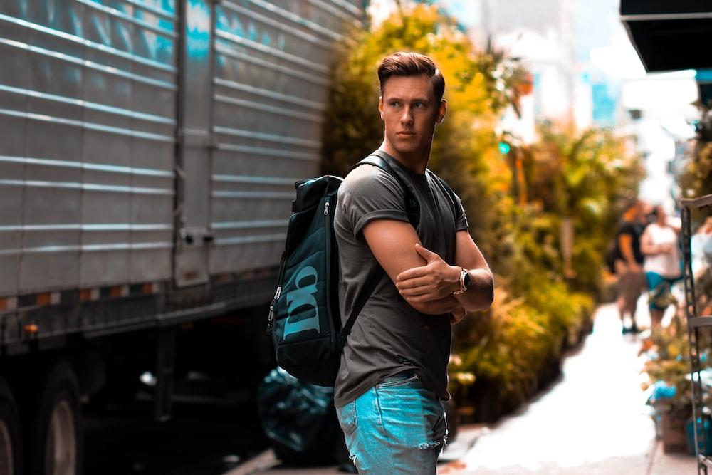 man wearing gray shirt and backpack