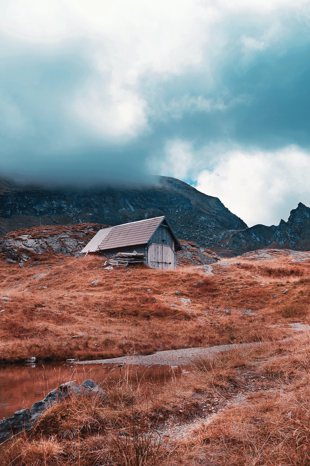 brown and gray wooden barn on brown grass field under cloudy sky at daytime