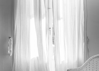 white window curtain hanging on black steel rod