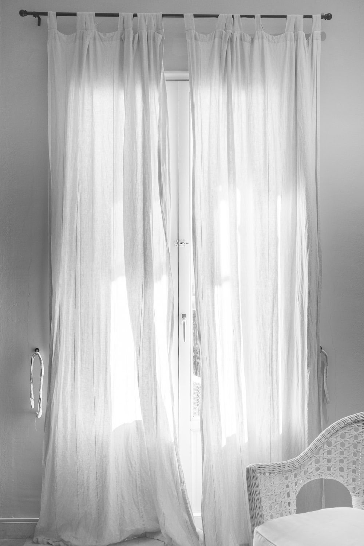 white window curtain hanging on black steel rod