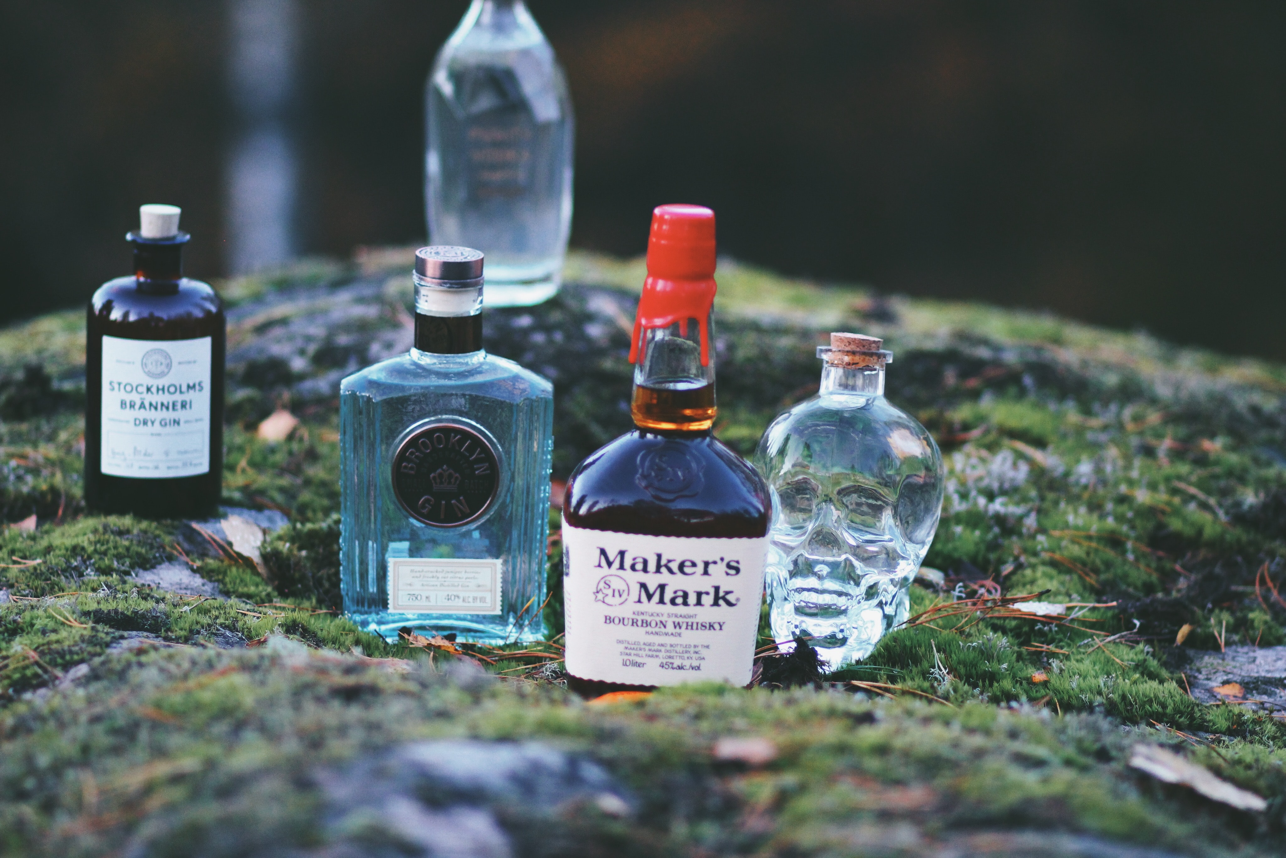 five assorted-brand bottles on top of grasses