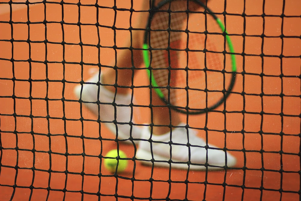 person wearing pair of white low-top sneakers while holding Wilson tennis racket