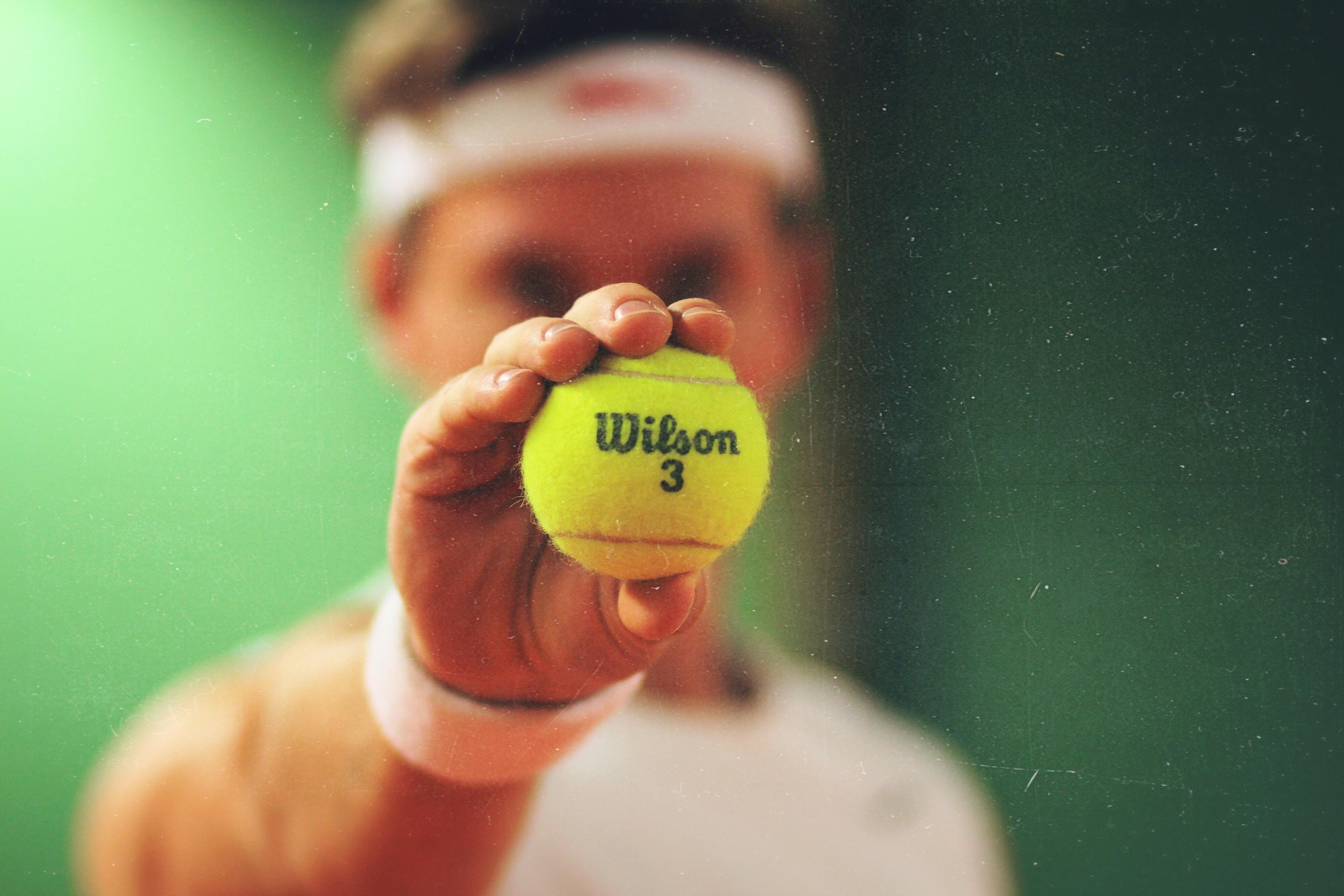 person holding green Wilson tennis ball