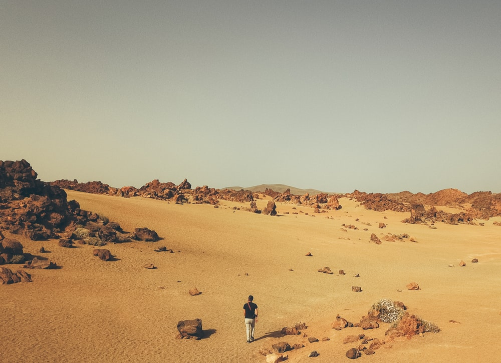 person walking on dirt and near boulders