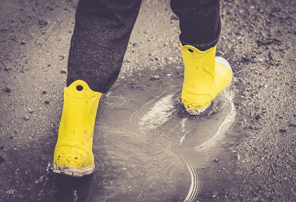 yellow rain boots on wet ground