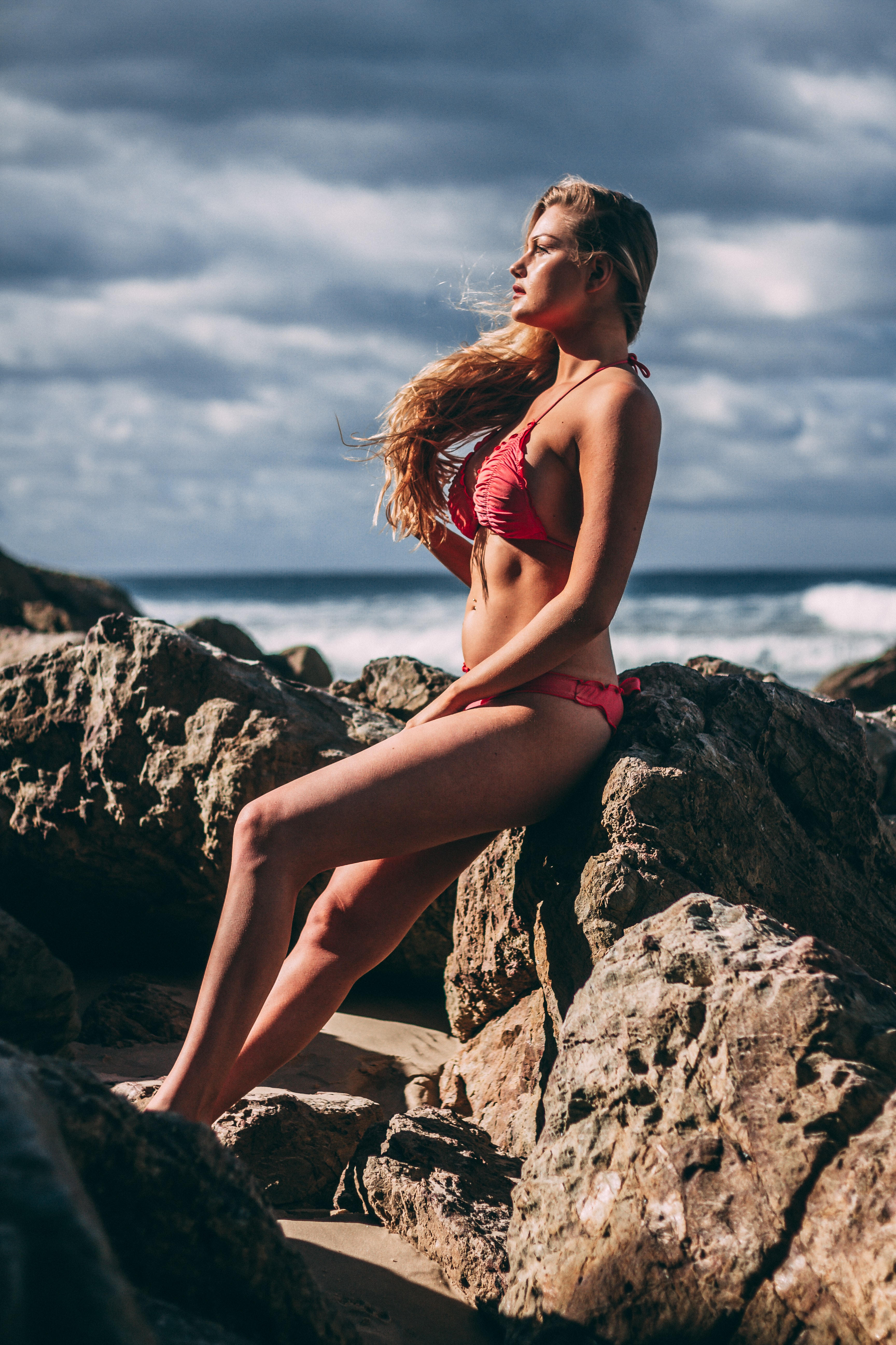 woman wearing bikini leaning on brown rock