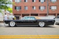 black sedan parked beside concrete building