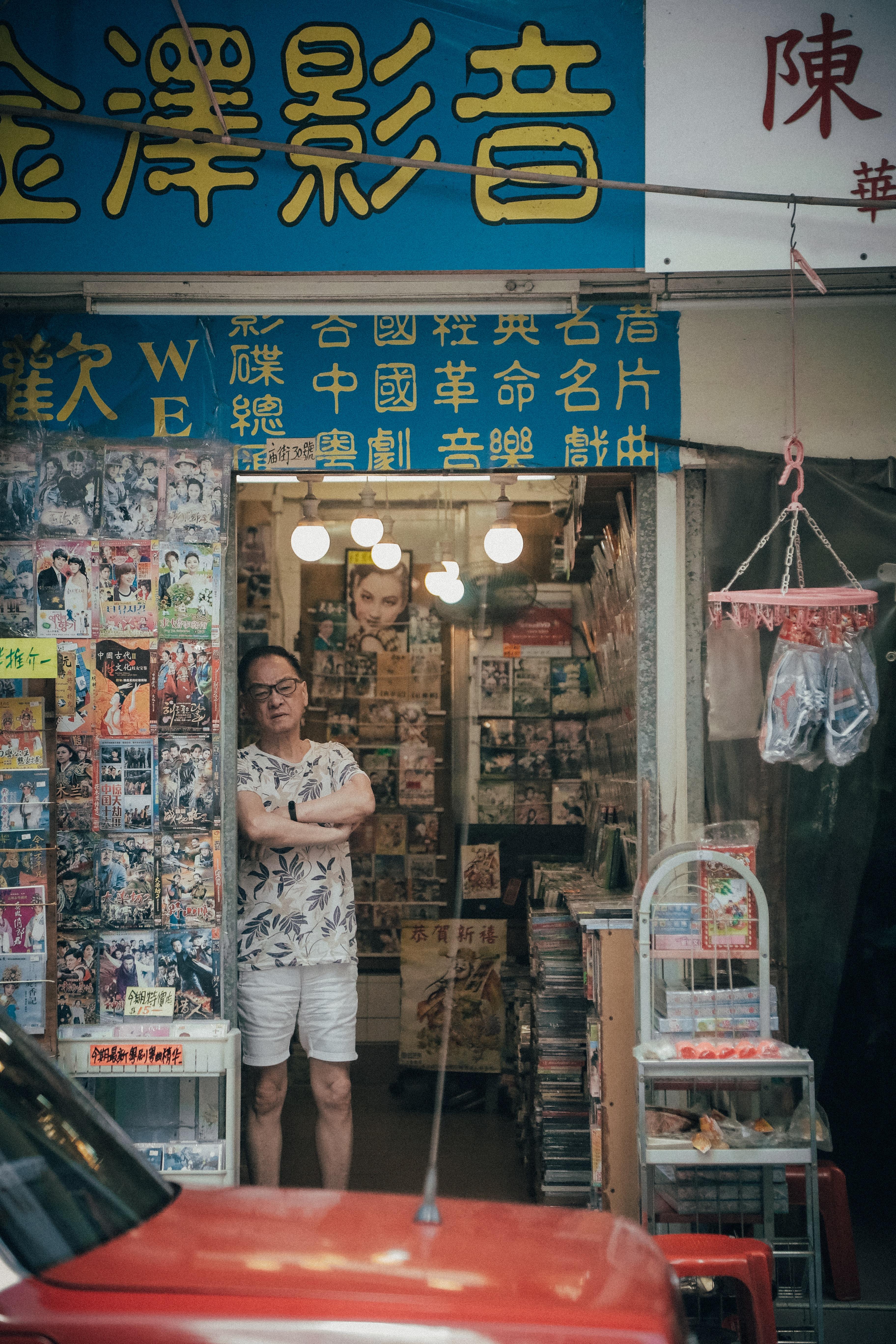 man standing beside assorted-title DVD case lot
