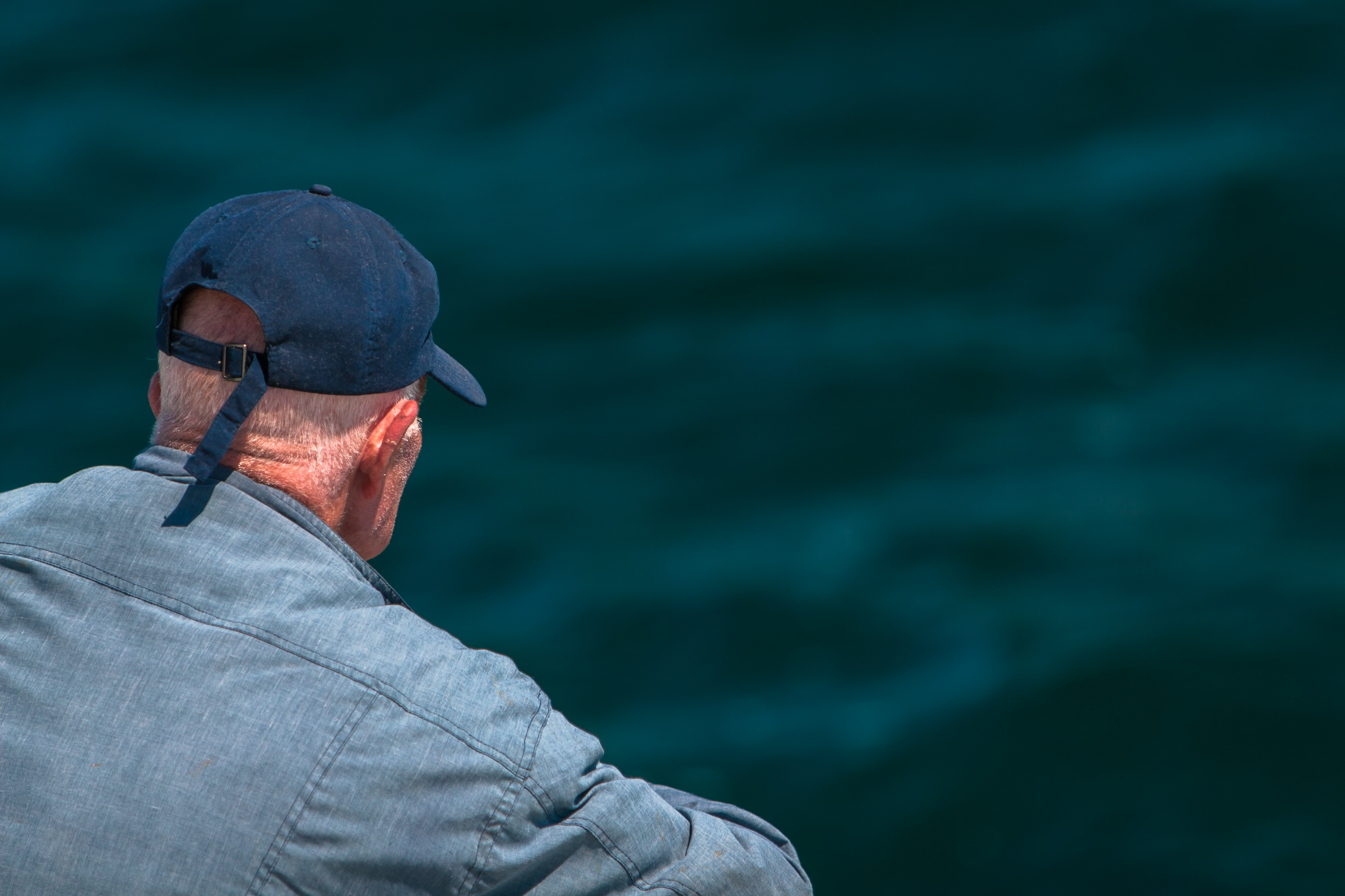 man looking on body of water wearing black cap