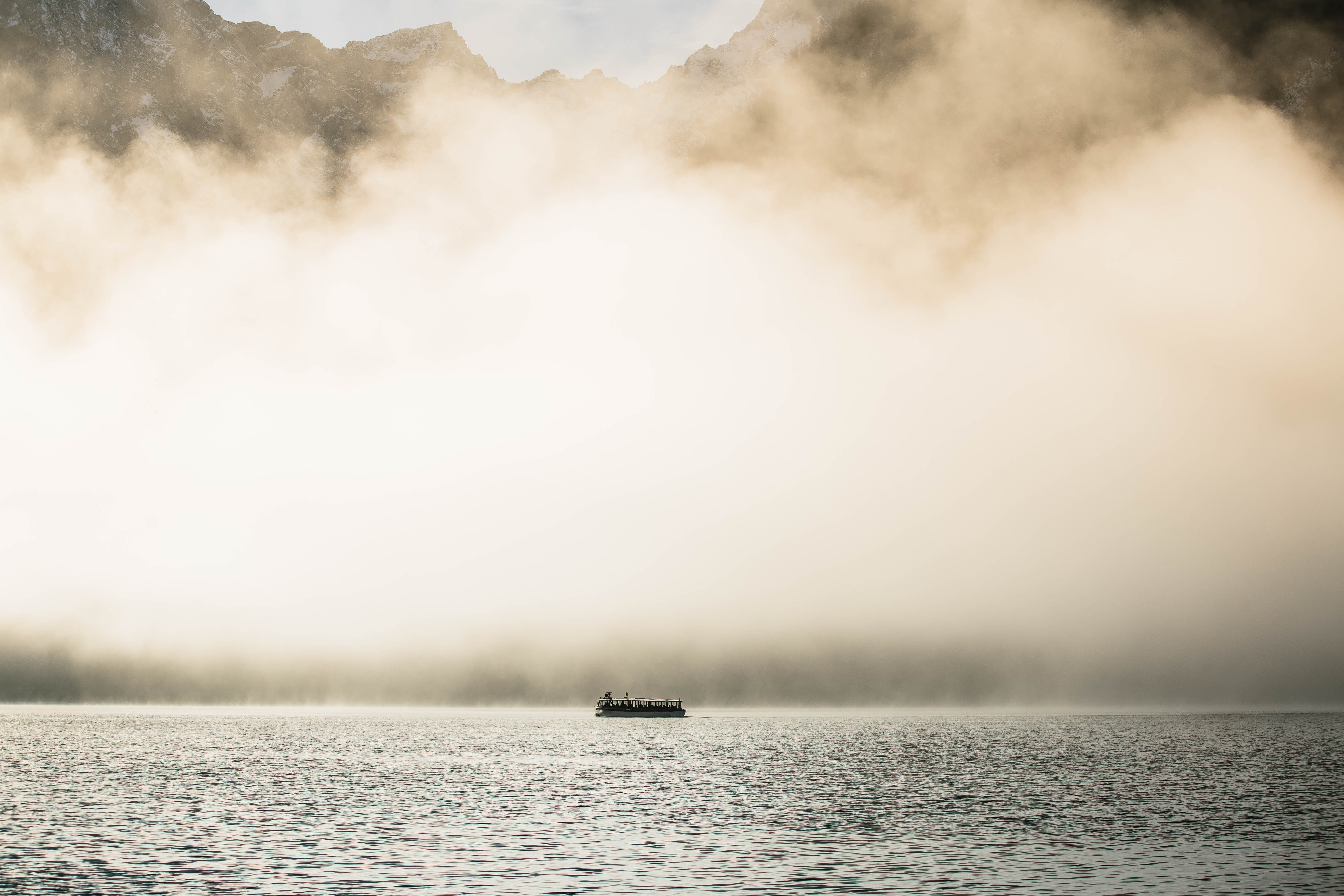 passenger boat under white clouds during daytime