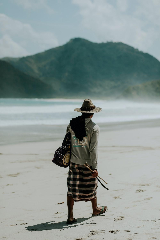man walking on shore under sunny sky