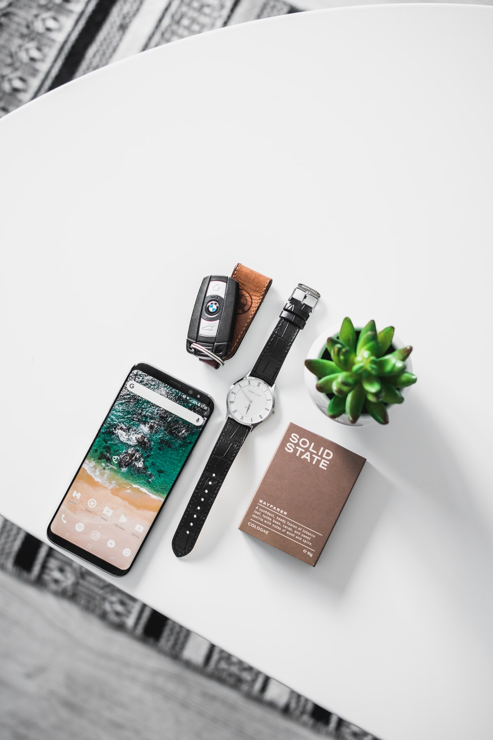 flat lay photography of watch, smartphone, car fob, and box