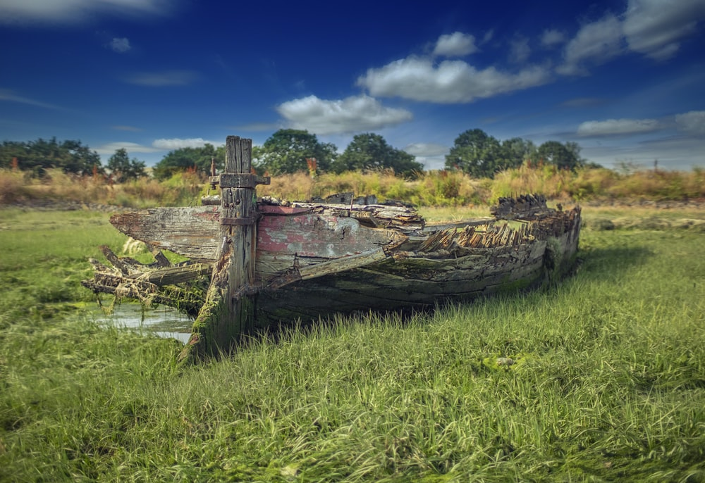 wrecked wooden boat on grass