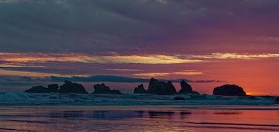 silhouette of rocks near seashore under orange and gray sky