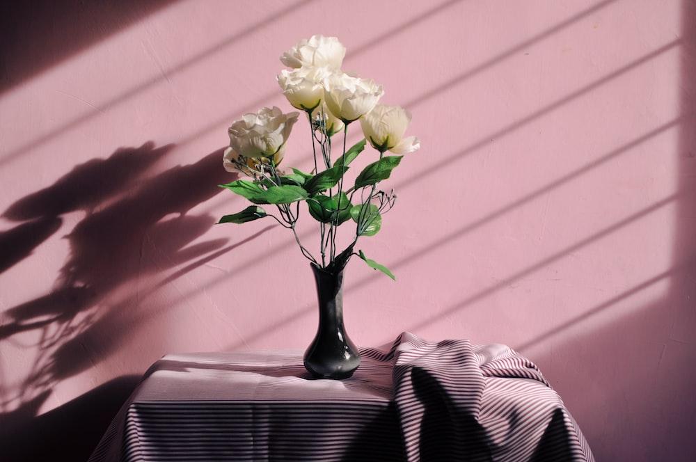 white artificial flowers in black vase