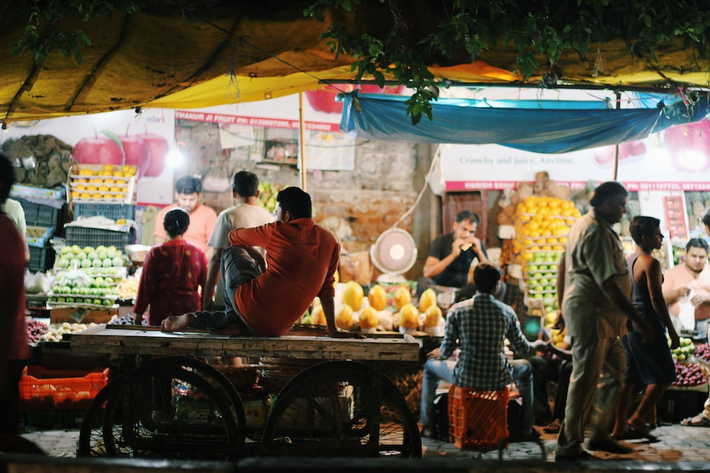 man sitting on top of table in front of vegetable and fruit stall
