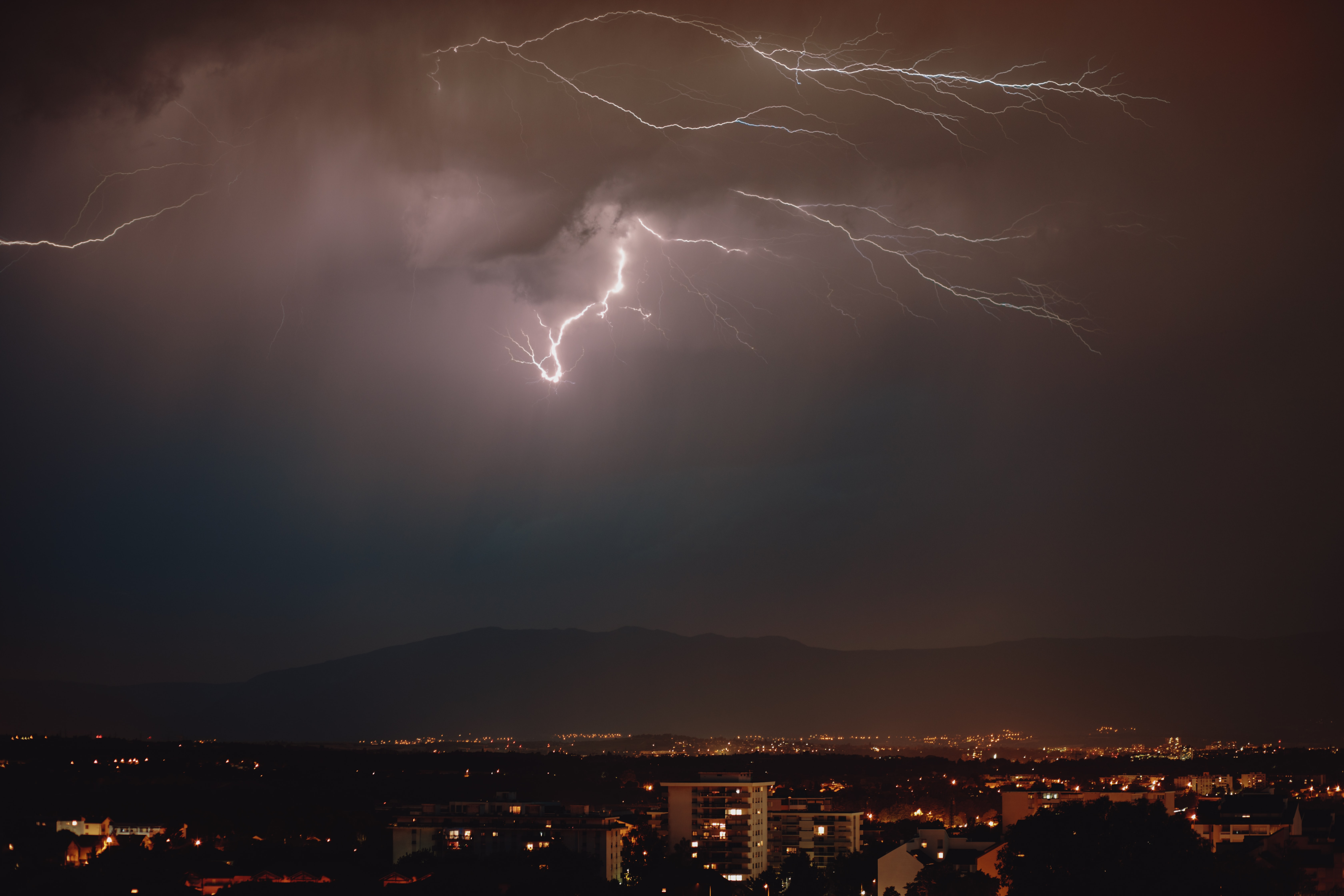lightning strike over the city during night time