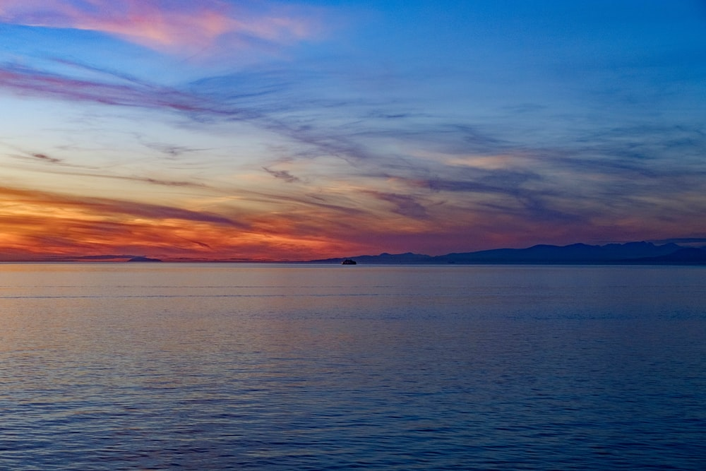 body of water under blue and orange sky