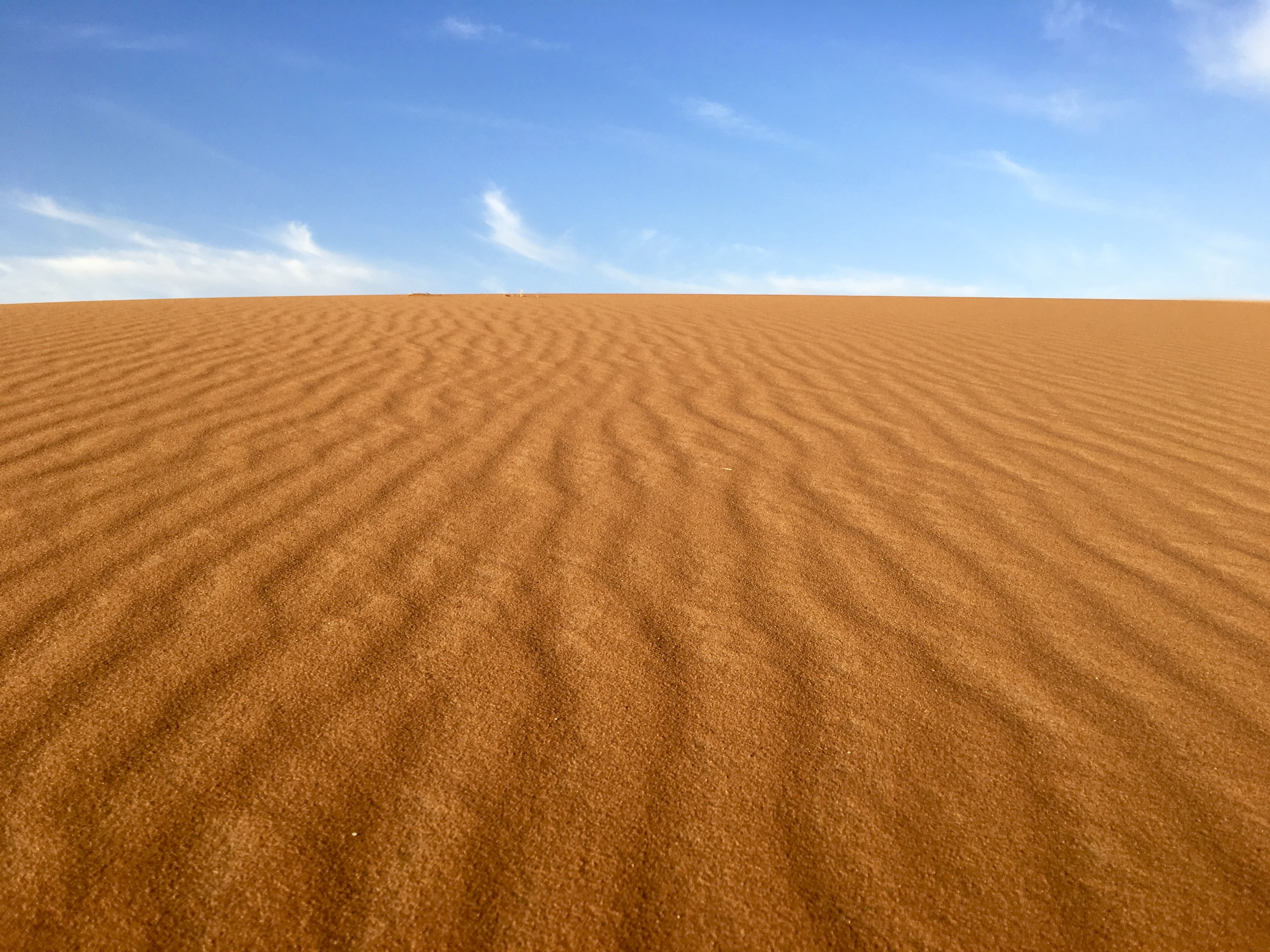 brown sand under blue and white sky
