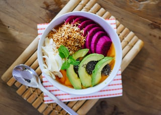 sliced fruits on bowl beside gray spoon