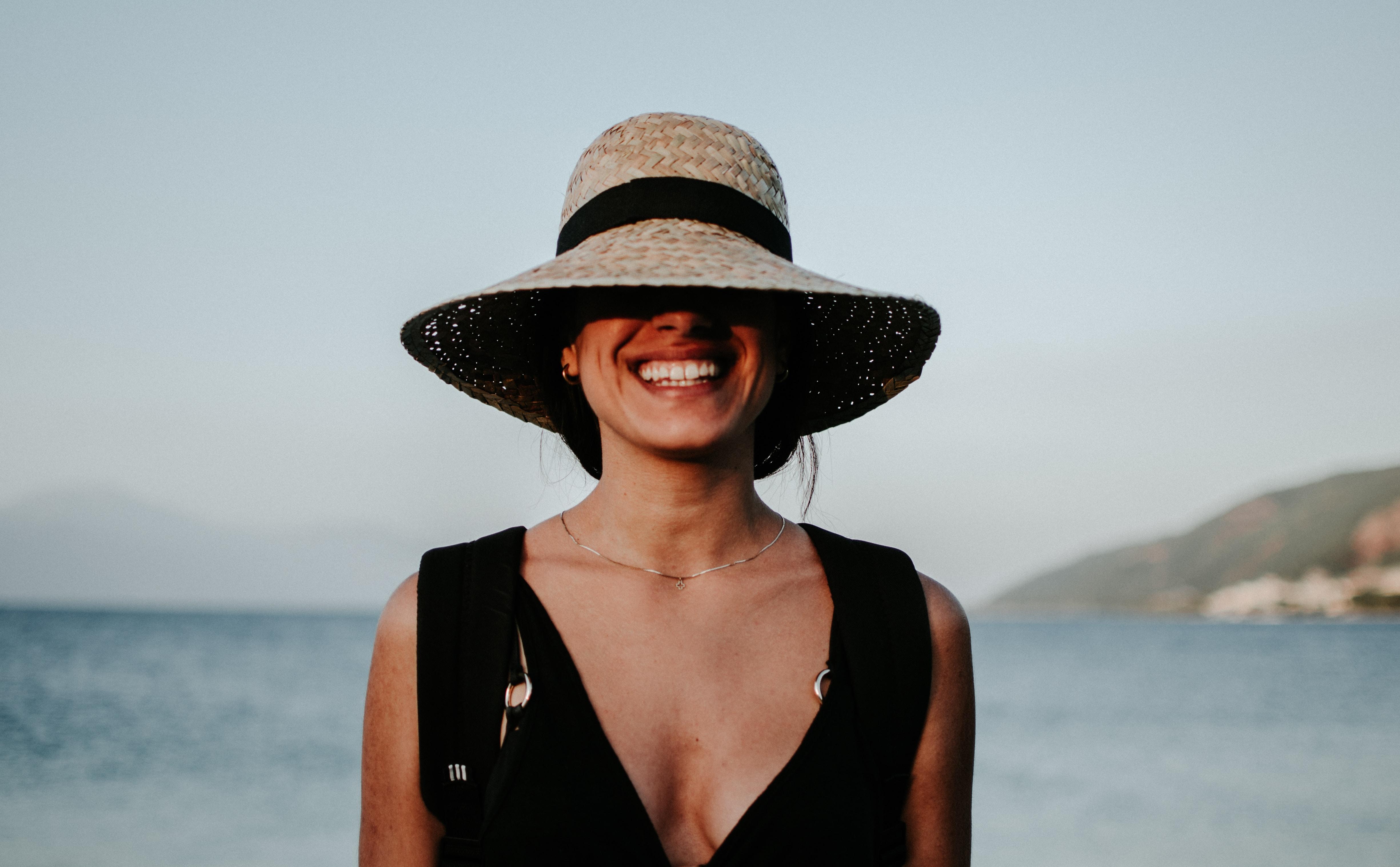 woman wearing sun hat while smiling