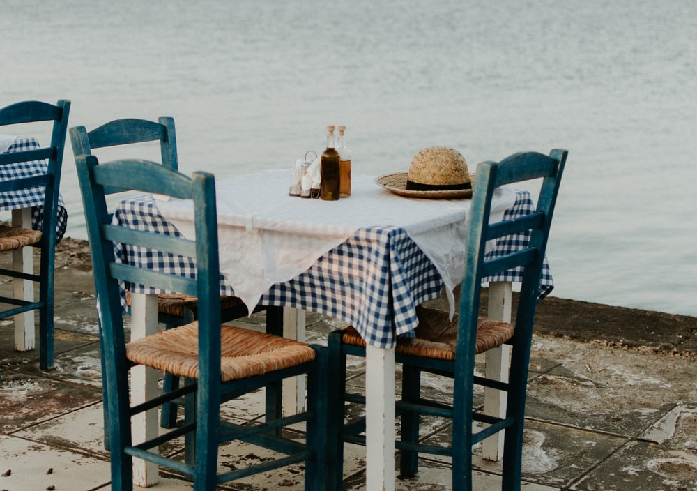 brown sun hat on top of table near calm water
