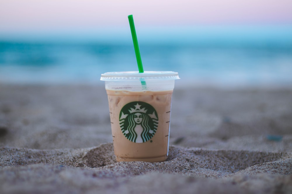 shallow focus photo of clear plastic Starbucks cup on sand