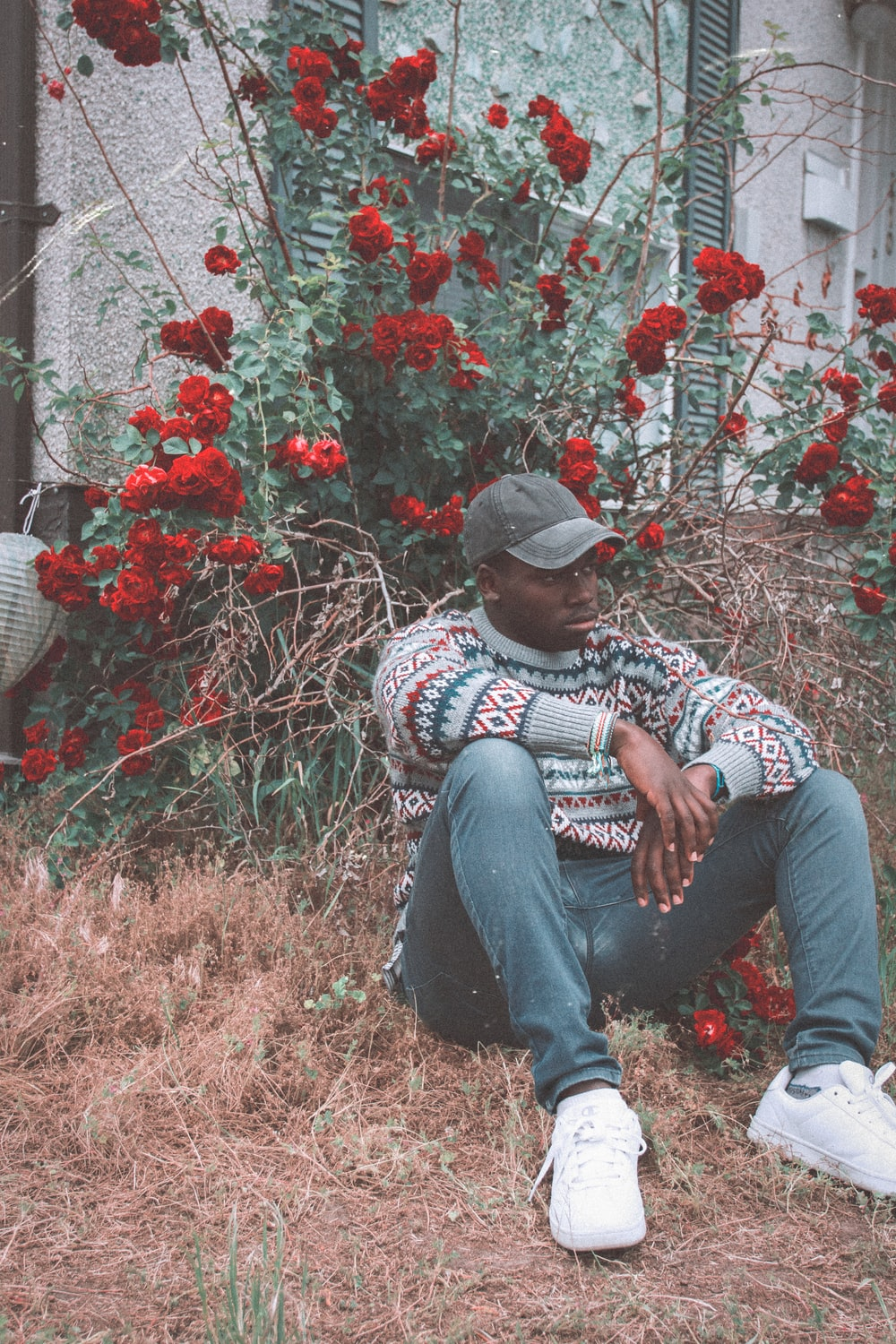 man sitting on grass in front of red flowered plant