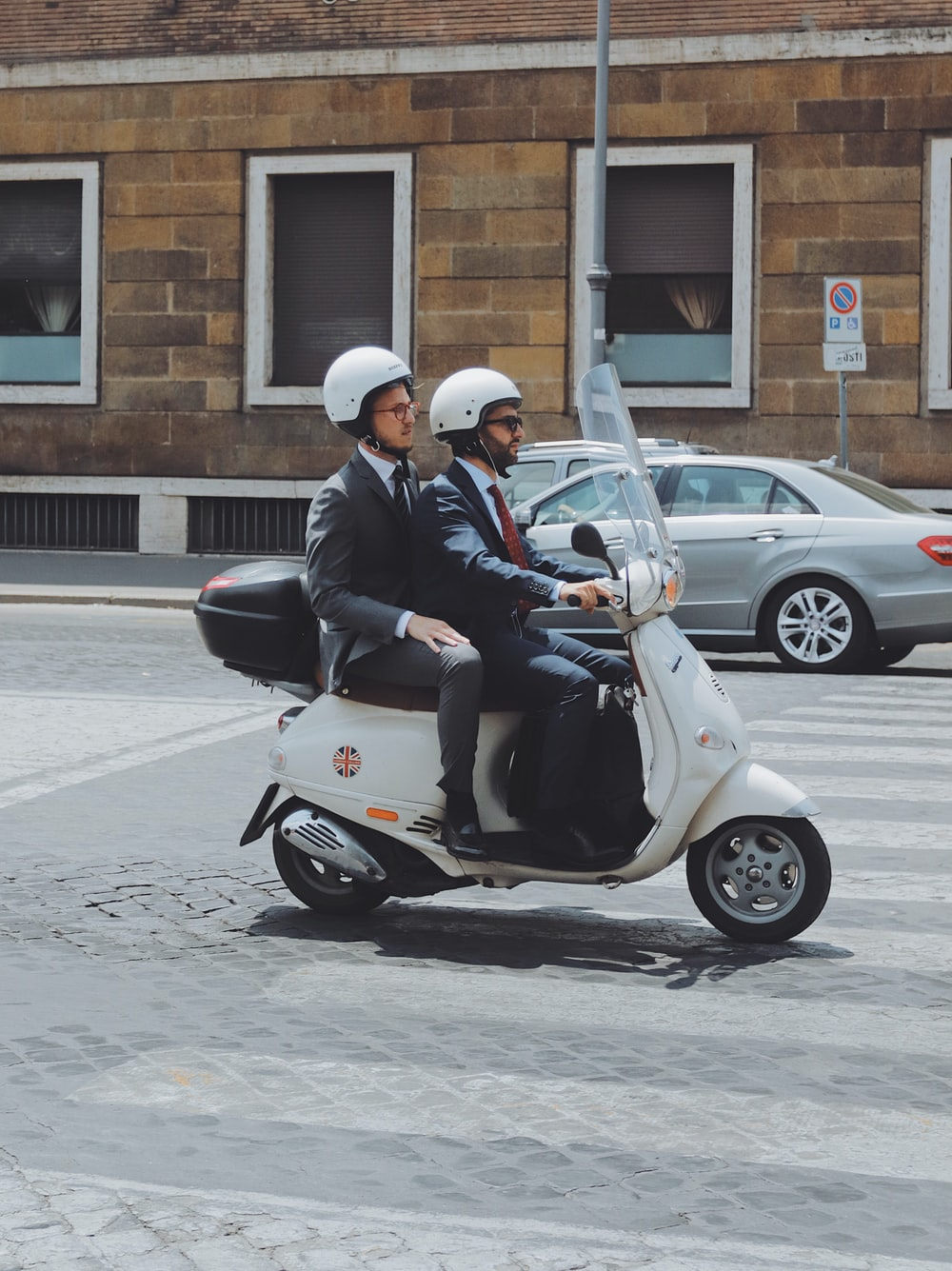 two men riding on motor scooter